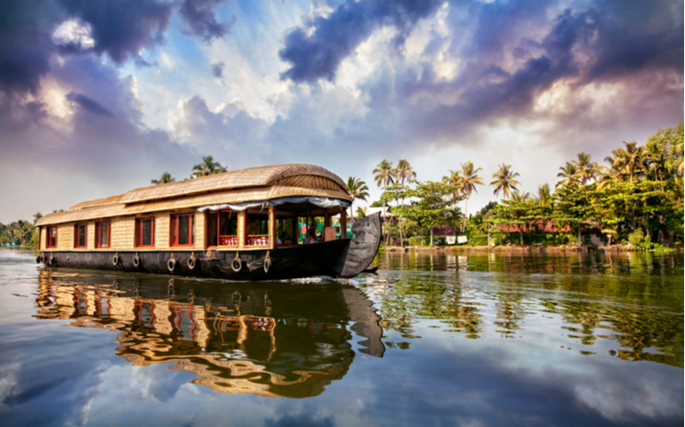 House boat in backwaters near palms at cloudy blue sky in Alappuzha, Kerala