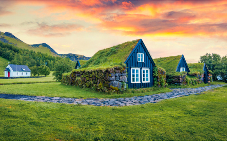 Typical view of turf-top houses in Icelandic countryside. Dramatic summer sunrise in Skogar village, south Iceland, Europe